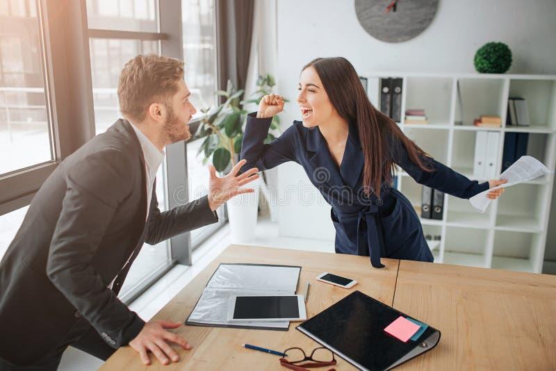 Discuta entre el hombre joven y la mujer Ella grita y lucha con el individuo Se colocan en sitio en la tabla Materiales que mient fotos de archivo libres de regalías