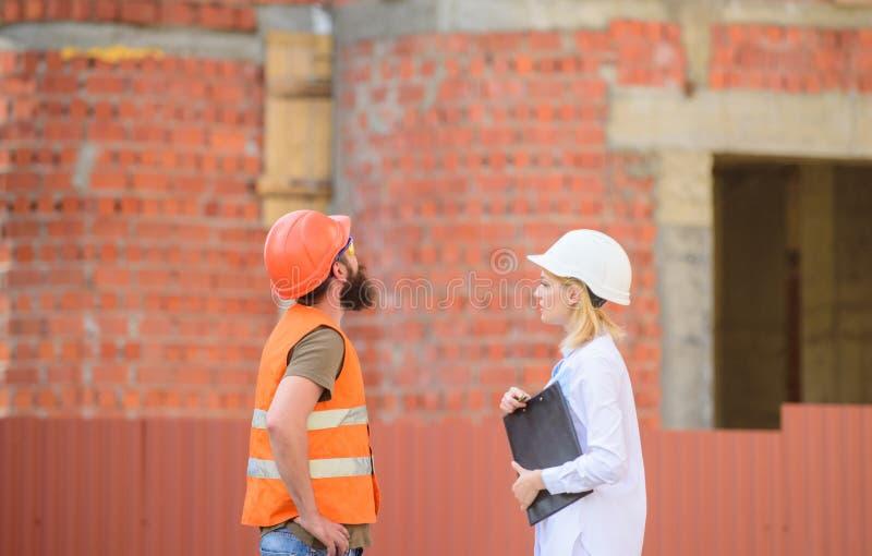 Discuta o projeto do progresso Conceito da indústria da construção civil Coordenador da mulher e construtor brutal farpado para d fotografia de stock