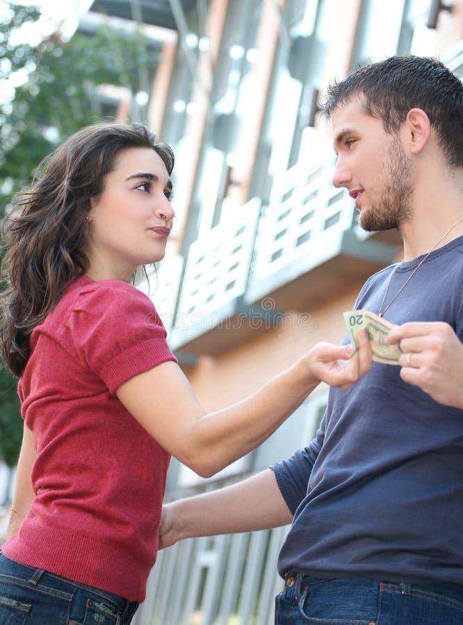 discuter l'argent de combat de couples au sujet des jeunes photographie stock libre de droits