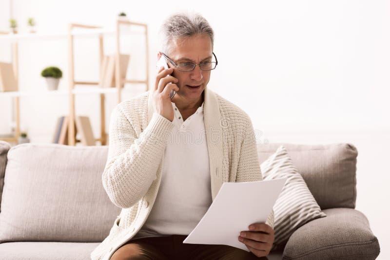 Discuter le document Homme mûr tenant le papier et parlant au téléphone photo stock
