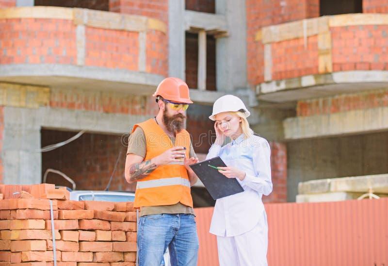Discuter le plan L'ingénieur et le constructeur de femme communiquent au chantier de construction Concept de communication d'équi photo libre de droits