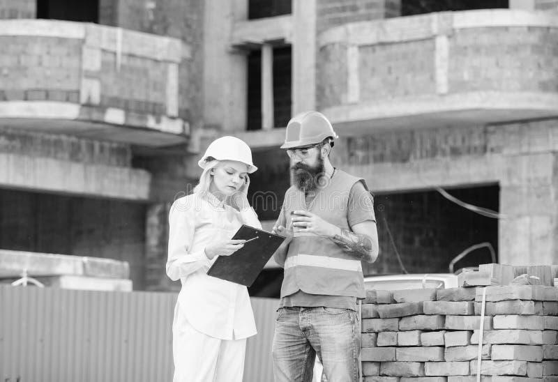 Discuter le plan L'ing?nieur et le constructeur de femme communiquent au chantier de construction Concept de communication d'?qui images stock