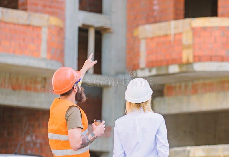 Discuter le plan L'ing?nieur et le constructeur de femme communiquent au chantier de construction Relations entre les clients de  image libre de droits