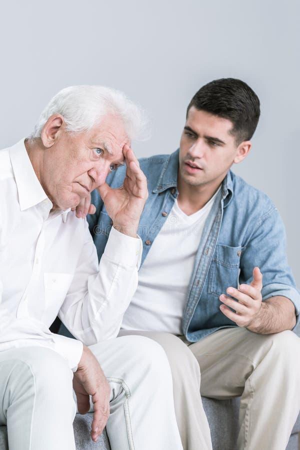 Discutez entre le petit-fils et le grand-père photographie stock libre de droits