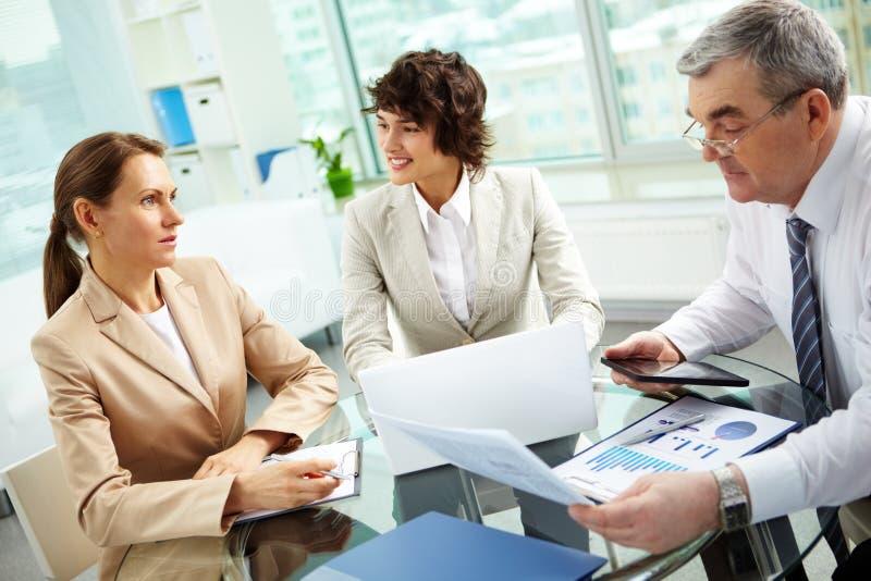 Discutindo matérias de negócio imagem de stock