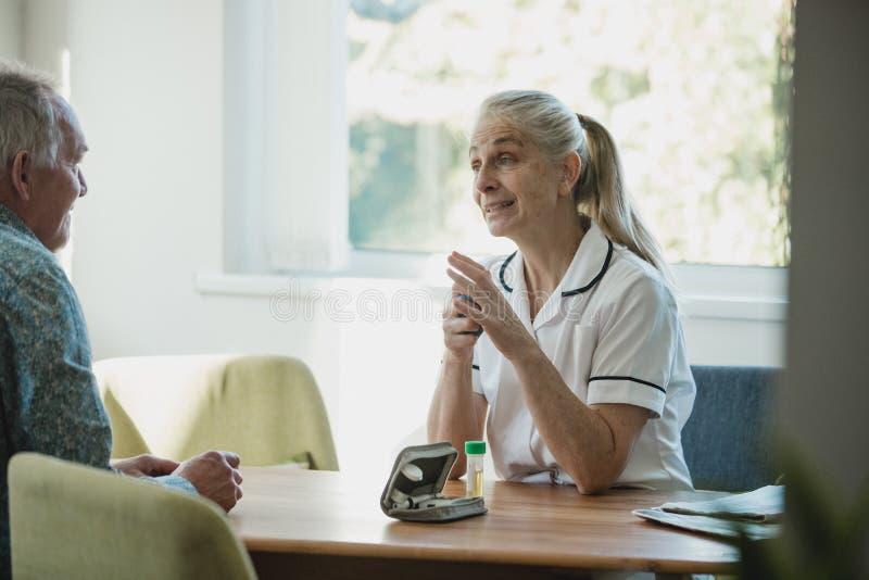 Discutindo o tratamento do diabetes com uma enfermeira do distrito foto de stock royalty free