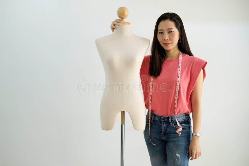 Diseñador asiático del paño de la mujer con el maniquí femenino en la tierra de la parte posterior del blanco imágenes de archivo libres de regalías