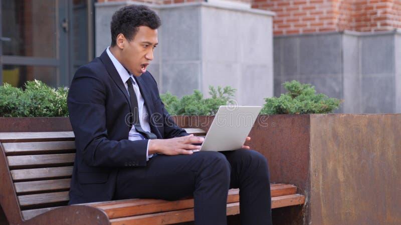 Diseñador asombroso Wondering mientras que usa el ordenador portátil que se sienta en banco fotos de archivo