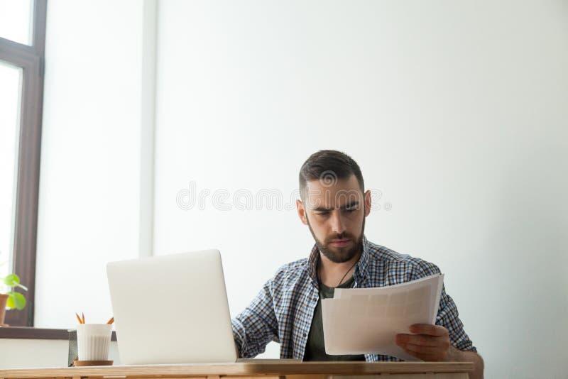 Diseñador barbudo concentrado con la paleta de la muestra del color del pantone foto de archivo