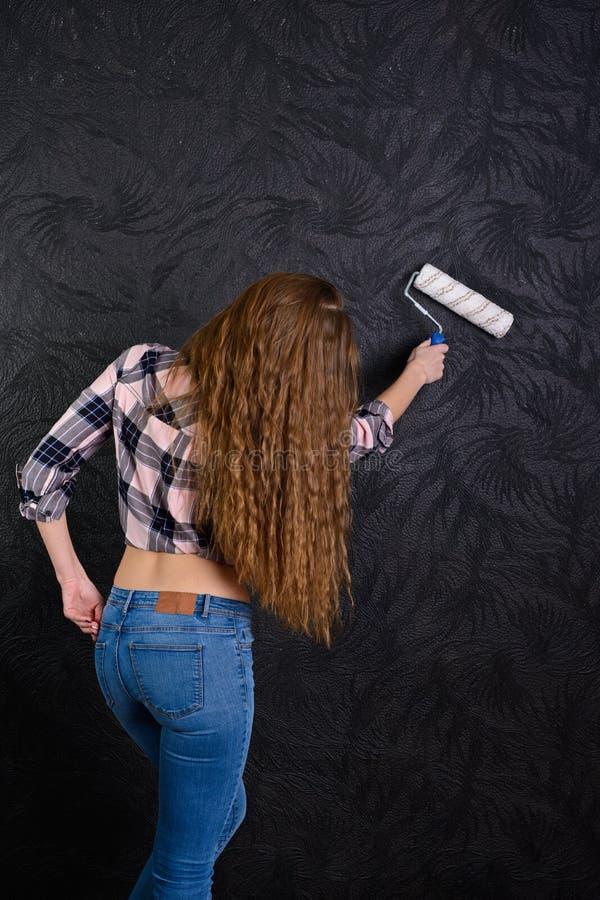 Diseñador de la muchacha con un rodillo de pintura a la pared imagenes de archivo