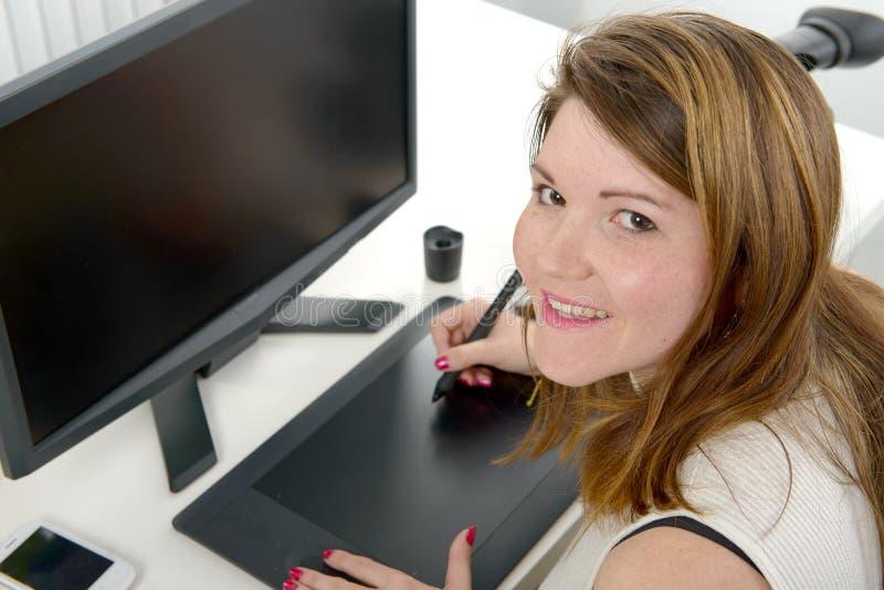 Diseñador de la mujer joven que usa la tableta de gráficos imagenes de archivo