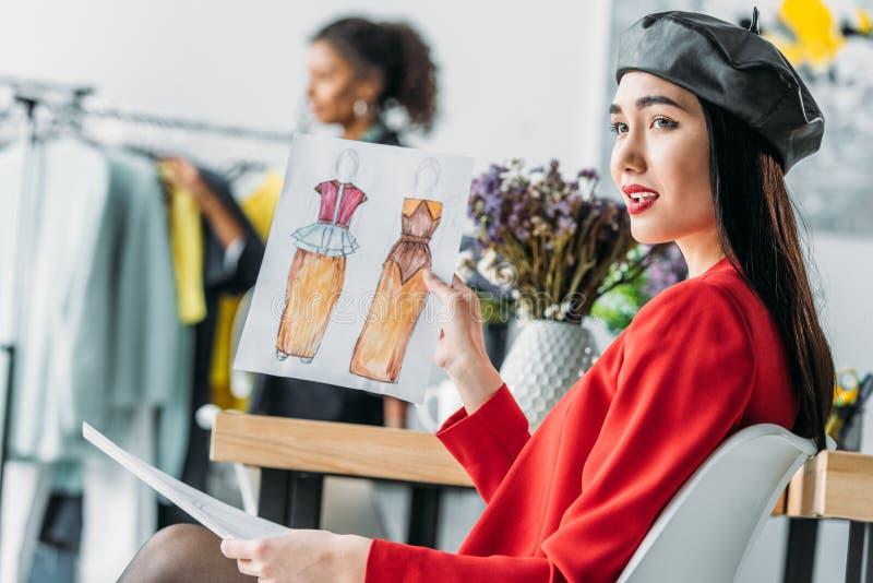 Diseñador de moda asiático con bosquejos imagenes de archivo