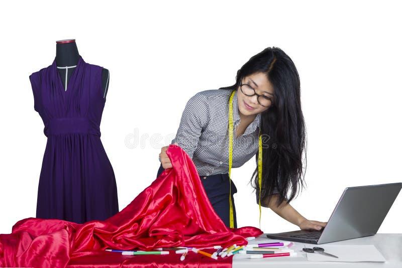 Diseñador de moda con la tela y el ordenador portátil imagen de archivo