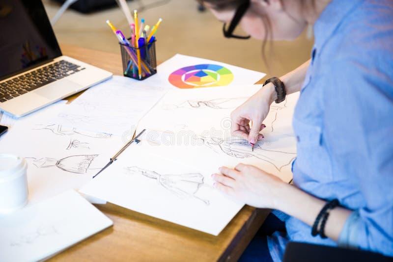 Diseñador de moda creativo de la mujer en los vidrios que sientan y que dibujan bosquejos foto de archivo libre de regalías