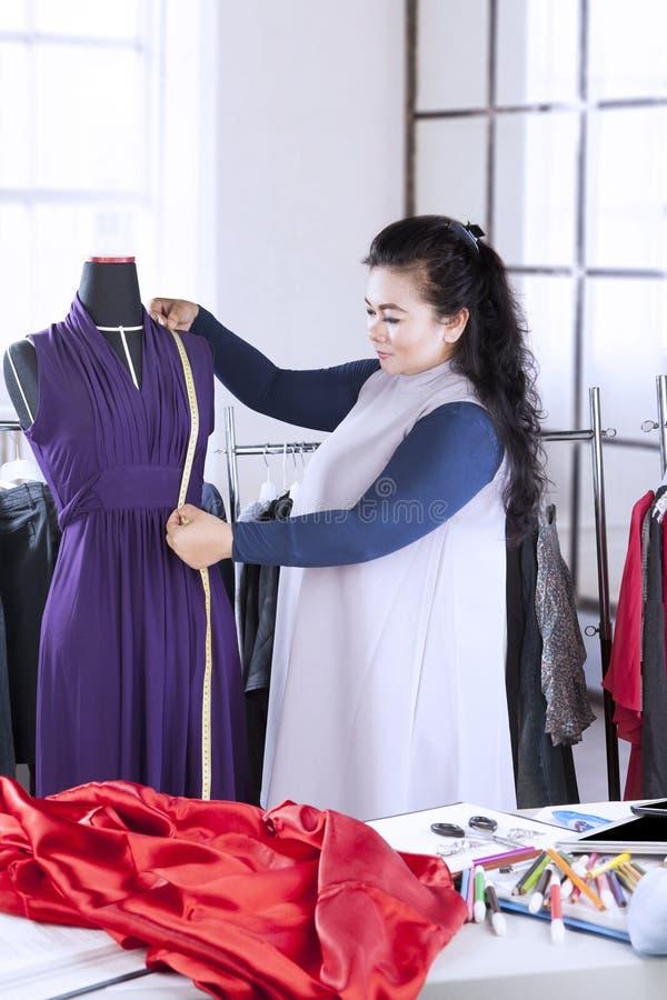 Diseñador de moda de sexo femenino que mide un vestido imagen de archivo