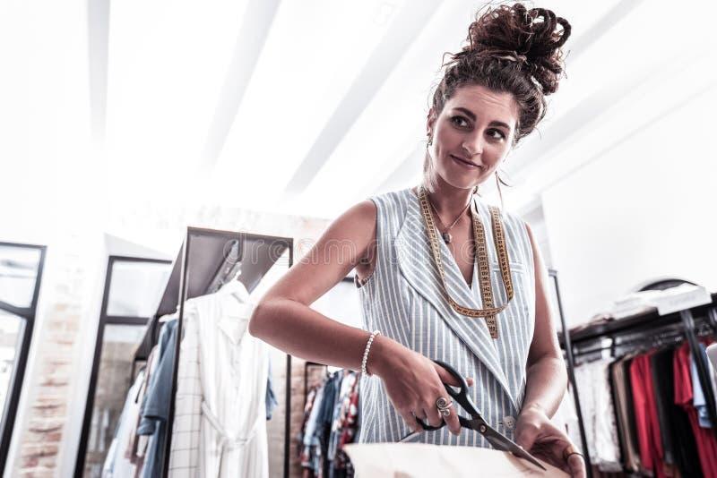 Diseñador de moda experto famoso que trabaja difícilmente en su taller mientras que teniendo inspiración imagen de archivo