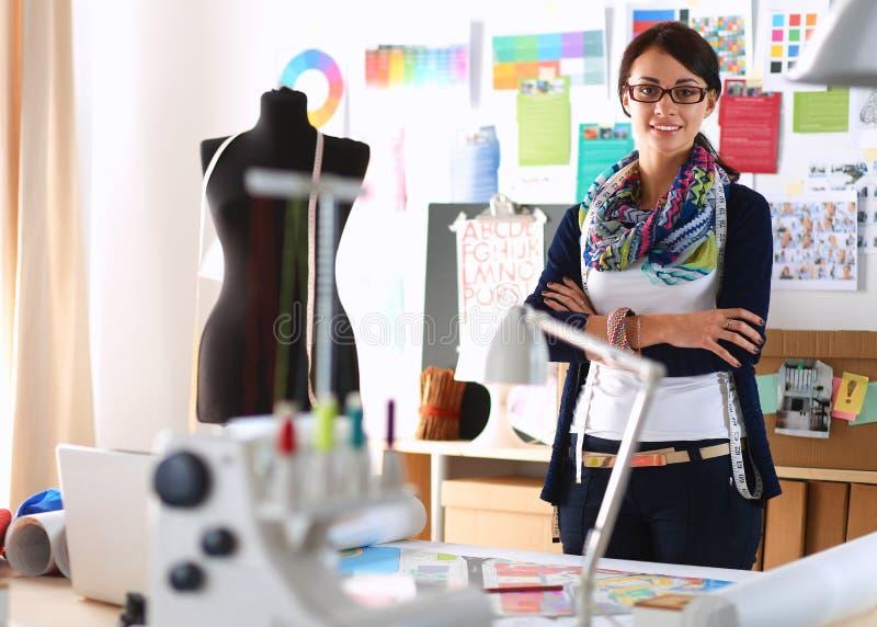 Diseñador de moda hermoso que se coloca en estudio foto de archivo