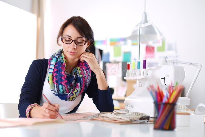 Diseñador de moda hermoso que se sienta en el escritorio en estudio fotografía de archivo libre de regalías