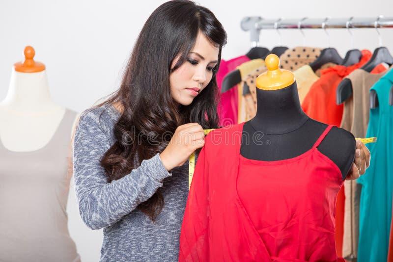 Diseñador de moda o sastre que trabaja en un diseño o un proyecto, ella Tak imagen de archivo libre de regalías