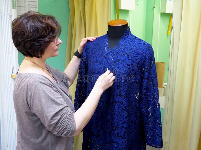 Diseñador de moda que mira en maniquí imagen de archivo libre de regalías
