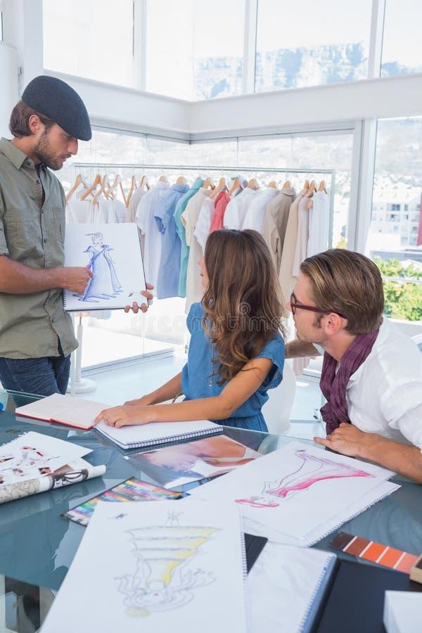Diseñador de moda que muestra un drenaje a su colega imagenes de archivo