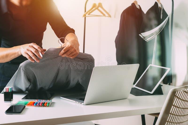 Diseñador de moda que sostiene la camisa y que usa el ordenador portátil con la etiqueta digital foto de archivo libre de regalías