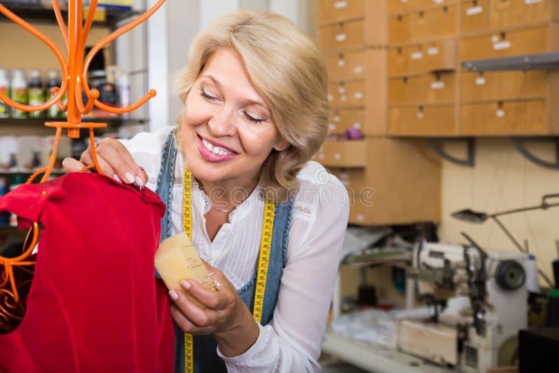 Diseñador de moda rubio de sexo femenino que dobladilla la nueva ropa en maniquí foto de archivo