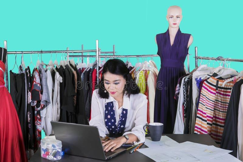 Diseñador de moda de sexo femenino que mecanografía en un ordenador portátil fotos de archivo libres de regalías