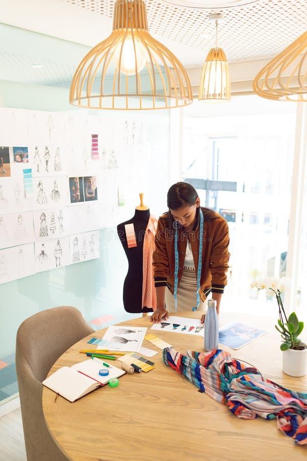 Diseñador de moda de sexo femenino que mira bosquejos en la tabla en una oficina moderna imagen de archivo