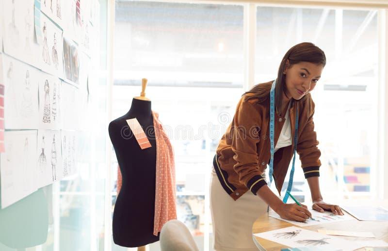 Diseñador de moda de sexo femenino que mira la cámara mientras que dibuja bosquejo en la tabla foto de archivo