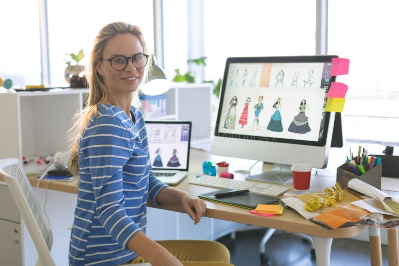 Dise?ador de moda de sexo femenino que mira la c?mara mientras que se sienta en el escritorio en una oficina moderna fotos de archivo libres de regalías