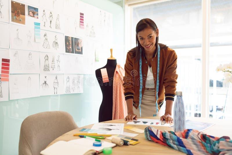 Diseñador de moda de sexo femenino que mira la cámara mientras que trabaja en la tabla en una oficina moderna fotografía de archivo