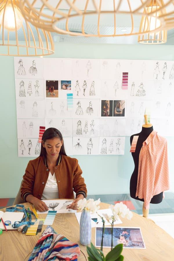 Diseñador de moda de sexo femenino que mira muestra del color en la tabla en una oficina moderna imagenes de archivo