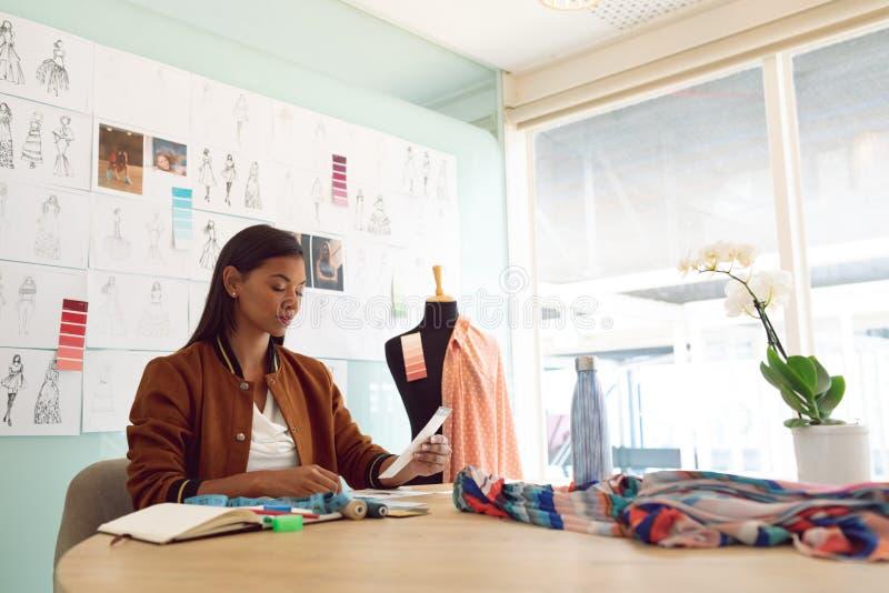 Diseñador de moda de sexo femenino que mira muestra del color en la tabla en una oficina moderna imagen de archivo libre de regalías