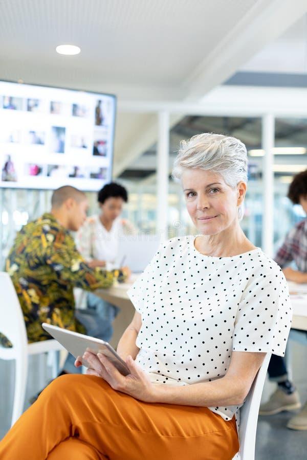 Diseñador de moda de sexo femenino que usa la tableta digital en la sala de conferencias en la oficina imágenes de archivo libres de regalías