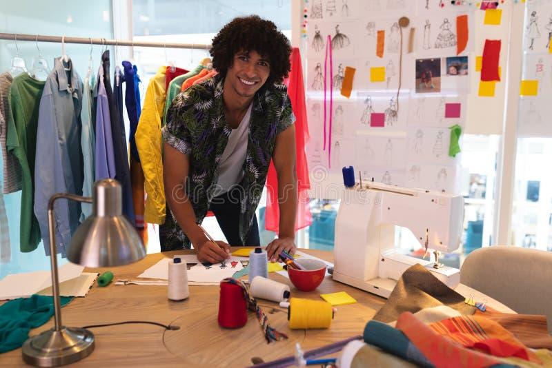 Diseñador de moda de sexo masculino que dibuja un bosquejo en el escritorio en estudio del diseño imagen de archivo libre de regalías