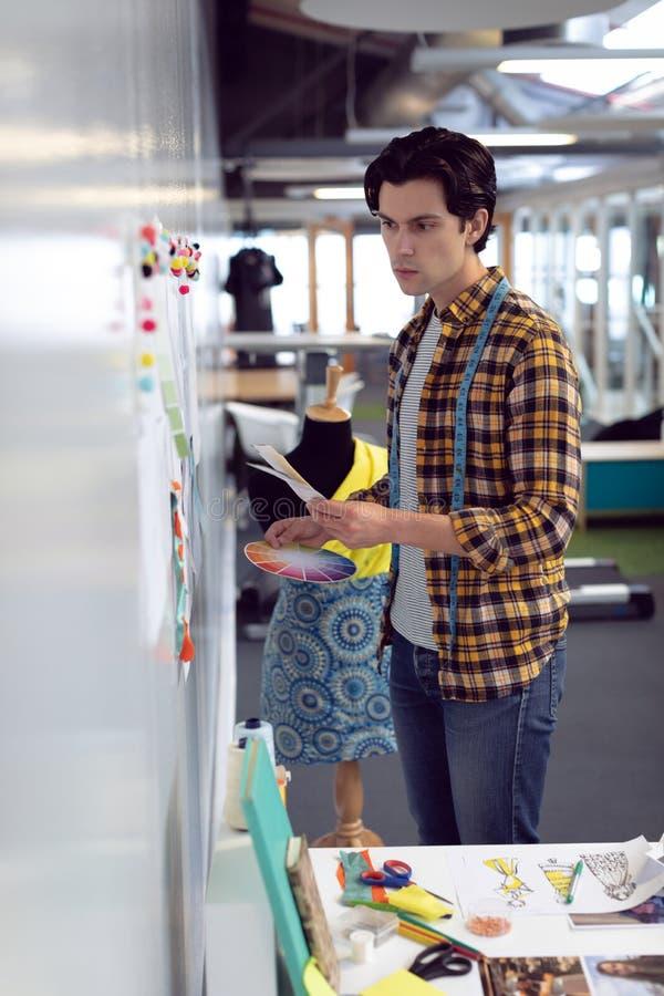 Diseñador de moda de sexo masculino que mira bosquejo en oficina imagen de archivo