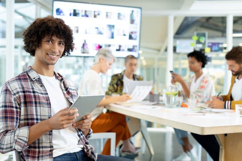 Diseñador de moda de sexo masculino que usa la tableta digital en la sala de conferencias en la oficina imagen de archivo