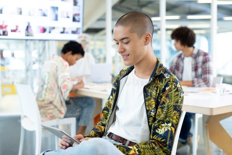 Diseñador de moda de sexo masculino que usa la tableta digital en la sala de conferencias imágenes de archivo libres de regalías