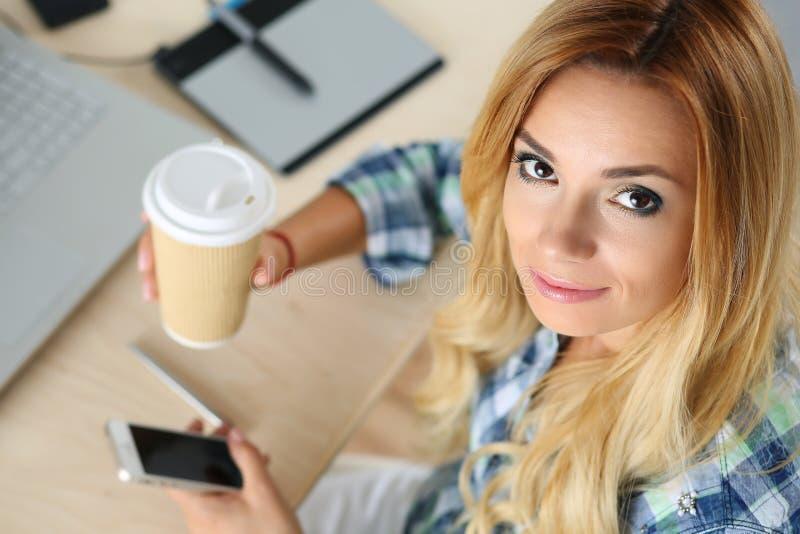Diseñador de sexo femenino en té de consumición de la mañana de la oficina fotos de archivo libres de regalías