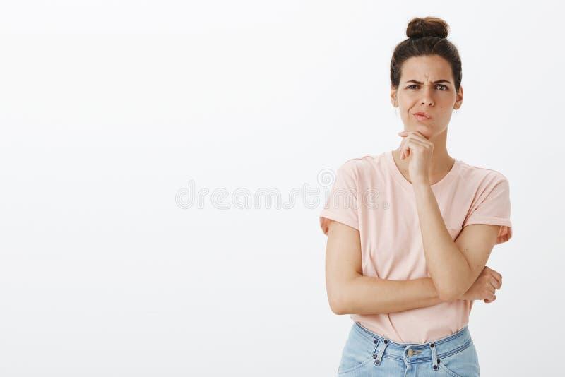 Diseñador de sexo femenino joven apuesto dudoso e inseguro con el bollo sucio smirking y que frunce el ceño como llevar a cabo la fotos de archivo