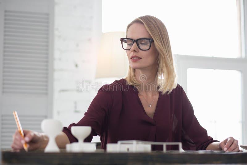 Diseñador de sexo femenino pensativo que anota pensamientos imagenes de archivo