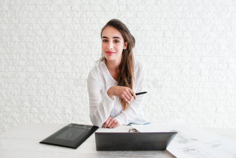 Diseñador de sexo femenino que mira la cámara en lugar de trabajo foto de archivo libre de regalías