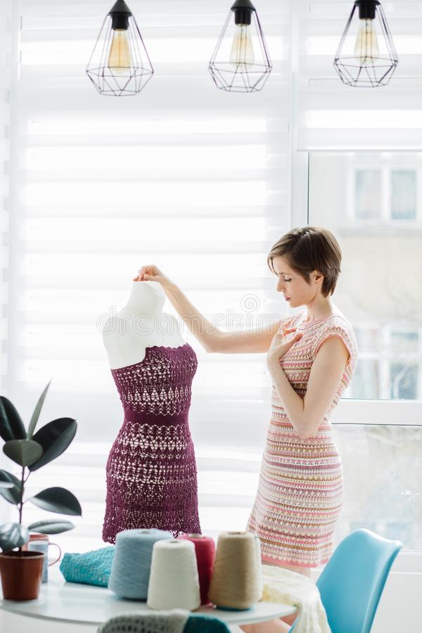 Diseñador de sexo femenino que trabaja con el vestido hecho punto en el interior acogedor del estudio, forma de vida independient foto de archivo