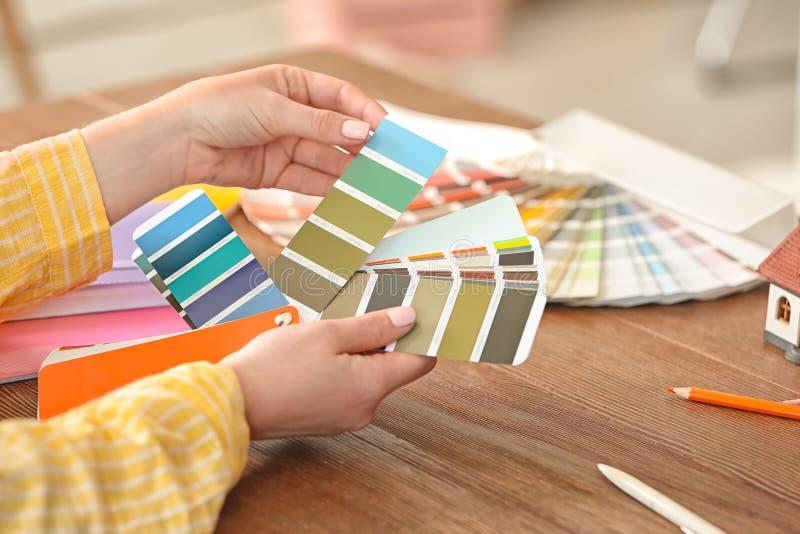 Diseñador de sexo femenino que trabaja con las muestras de la paleta de colores foto de archivo
