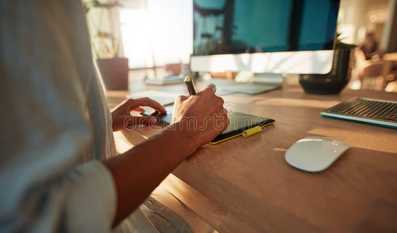 Diseñador de sexo femenino que usa la pluma de la tableta gráfica y de la aguja fotos de archivo libres de regalías