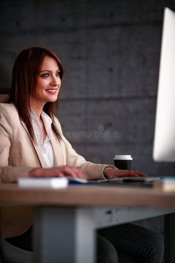 Diseñador de sexo femenino sonriente que usa el ordenador en oficina imagen de archivo libre de regalías