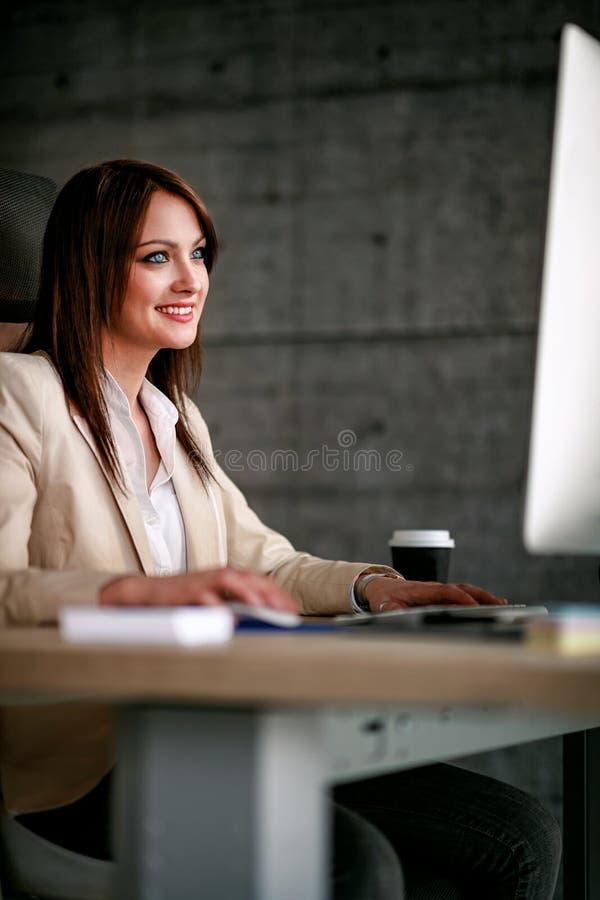 Diseñador de sexo femenino sonriente que usa el ordenador en oficina imagenes de archivo