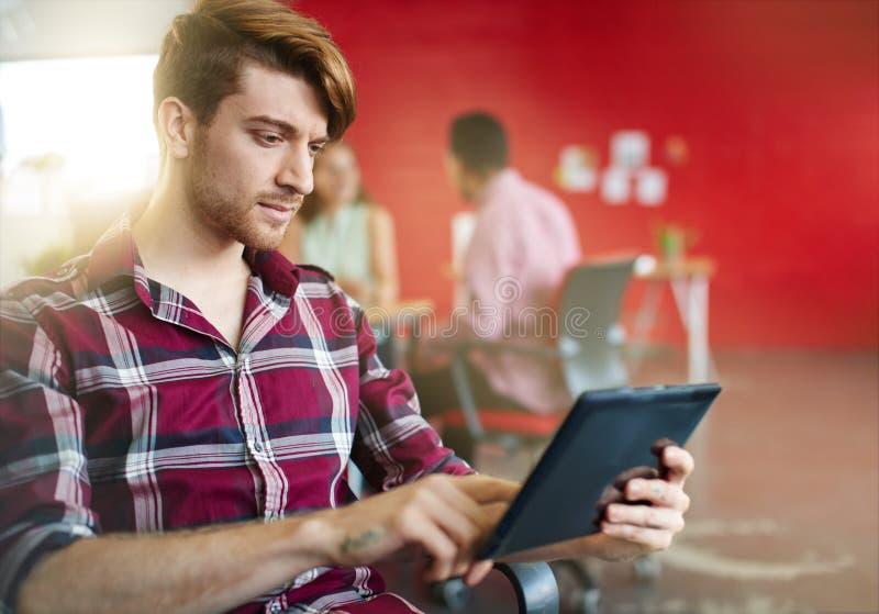Diseñador de sexo masculino confiado que trabaja en una tableta digital en espacio de oficina creativo rojo imagenes de archivo