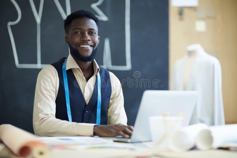 Diseñador de sexo masculino feliz de la ropa que usa el ordenador portátil en estudio foto de archivo